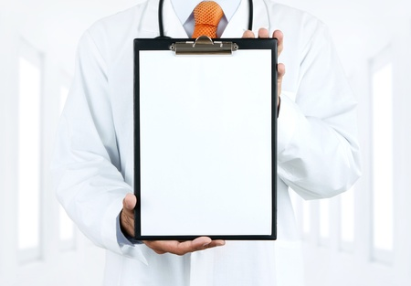 Doctor at hospital holding blank clipboard with copy space photo
