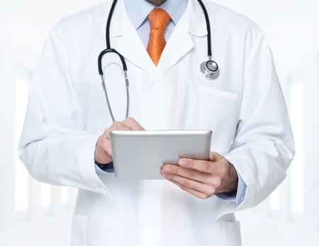 medical profession: Doctor at hospital working on a digital tablet