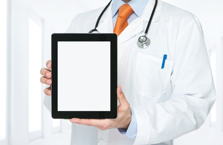 Doctor at hospital holding blank digital tablet with clipping path for the screen photo