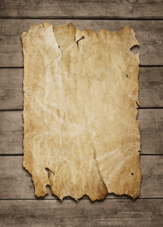 Old paper sheet nailed to a grunge wooden background with copy space photo