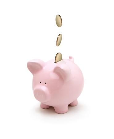 bankkonto: Goldene M�nzen fallen in ein Sparschwein isoliert auf wei�em Hintergrund