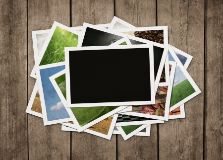 photo gallery: Stack of old photographs at grunge wooden background with clipping path for the blank one Stock Photo