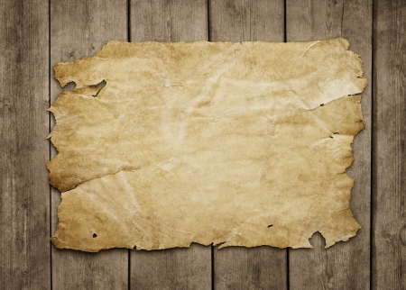 Old paper sheet at grunge wooden background with copy space photo