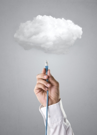 cable telefono: Mano masculina sobre fondo gris cable de conexi�n a la nube Foto de archivo