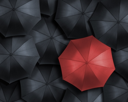 Standing out from the crowd, high angle view of red umbrella over many dark ones photo