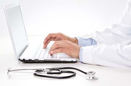Close up of male doctor s hands typing on an laptop photo