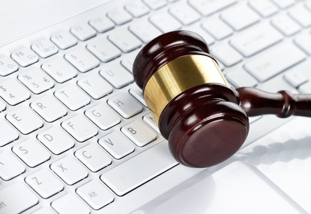 security laws: Close up of wooden gavel at the computer keyboard