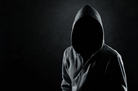 oscuro: Silueta del hombre con capucha o hooligan