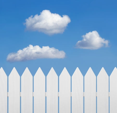 picket fence: White wooden fence against blue sky with copy space Stock Photo