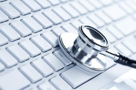 virus informatico: Silver estetoscopio acostado en un ordenador port�til, azul tonificado Foto de archivo