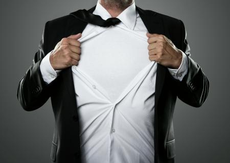 Joven hombre de negocios que actúa como un súper héroe y rasgando su camisa