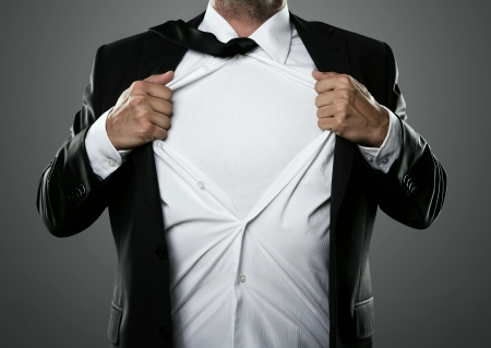 Young businessman acting like a super hero and tearing his shirt off photo