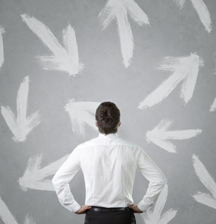 Jonge zakenman kijken naar vele pijlen wees in verschillende richtingen