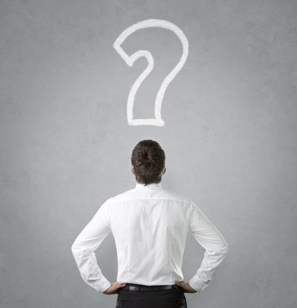 confundido: Joven hombre de negocios mirando tiza dibujado signo de interrogaci�n