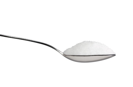 Salt or sugar on a teaspoon isolated on white background photo