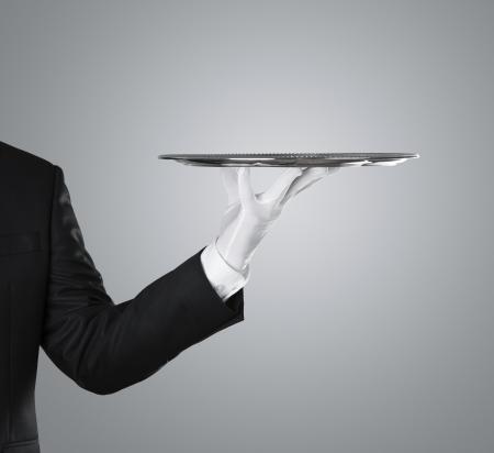 Camarero que sostiene la bandeja de plata vacía sobre fondo gris, con copia espacio