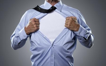 Joven empresario rasgado la camisa aislado en fondo gris con el espacio de la copia