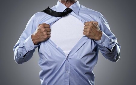Young businessman tearing his shirt off isolated on gray background with copy space photo