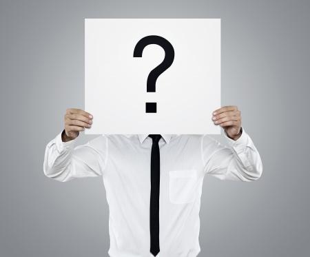 punto interrogativo: Giovane uomo d'affari che tiene scheda bianca con il punto interrogativo su di esso isolato su sfondo grigio