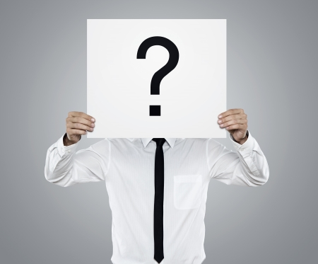 questions answers: Young businessman holding white card with question mark on it isolated on gray background