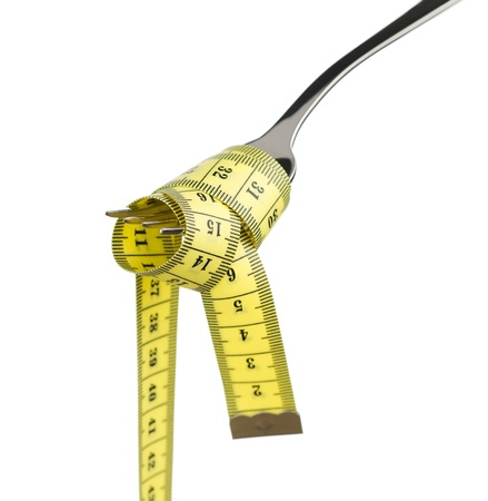 Diet concept, tape measure on silver fork as a spaghetti isolated on white background photo