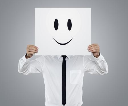 caras chistosas: Joven hombre de negocios que sostiene la tarjeta con una cara feliz en �l aislados en fondo gris