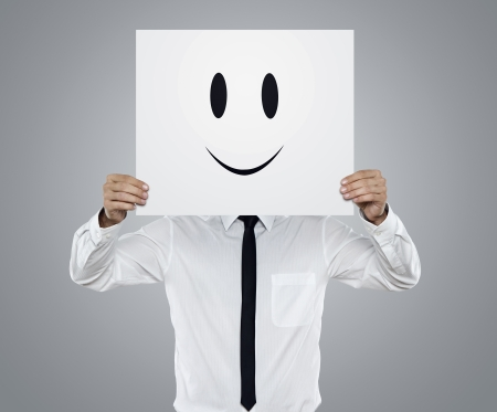 face to face: Young businessman holding card with a happy face on it isolated on gray background