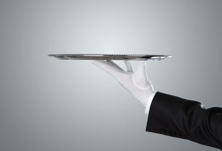 Kelner die leeg zilveren dienblad over grijze achtergrond met een kopie ruimte Stockfoto