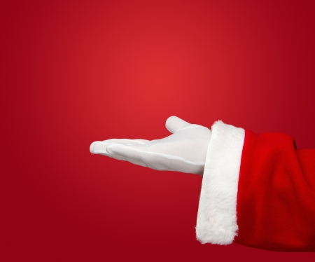 claus: Santa Claus hand presenting your text or product over red background