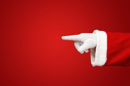 Santa s hand pointing your text or product over red background with copy space photo