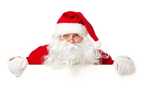 �santaclaus: Pap� Noel feliz mirando desde detr�s de la se�al en blanco aislado en fondo blanco, con copia espacio Foto de archivo