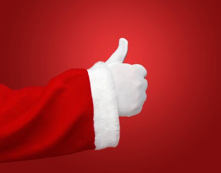 give hand: Santa Claus hand showing thumbs up over red background with copy space Stock Photo