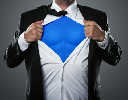 Joven hombre de negocios que actúa como un súper héroe y rasgando su camisa con copia espacio