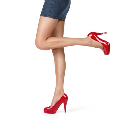 Close up of elegant female legs with red high heels, walking, isolated on white background photo