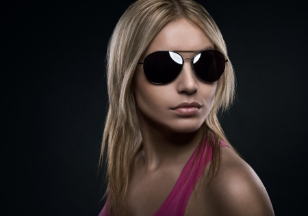 Blonde beautiful woman with sunglasses over dark concrete background with copy space photo