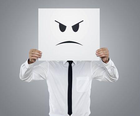 enojo: Joven hombre de negocios que sostiene la tarjeta con una cara enojada en �l aislados en fondo gris
