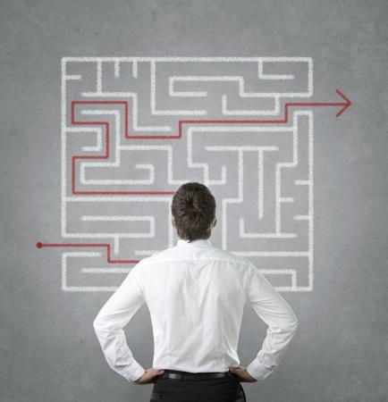 Confus jeune homme d'affaires regardant le labyrinthe sur le mur