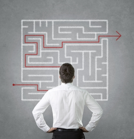 Verward jonge zakenman zoekt op het labyrint aan de muur