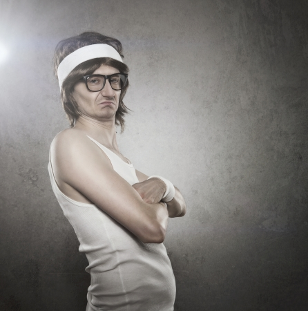 stupid body: Retro sport nerd with serious face expression acting like a tough guy over gray background with copy space