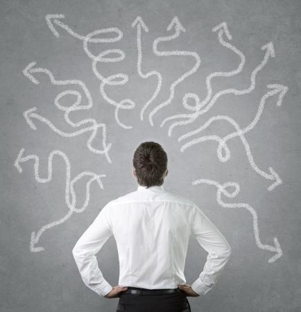 confus: Confus, jeune homme d'affaires regardant nombreuses fl�ches tordues sur le mur de b�ton Banque d'images