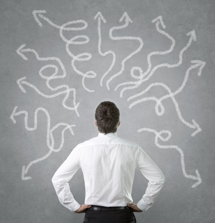 persona confundida: Hombre de negocios confuso, joven mirando muchas flechas torcidas en el muro de hormigón Foto de archivo