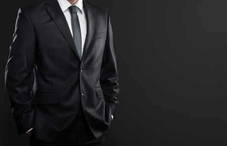 tux: Close up of businessman in suit over dark gray background with copy space