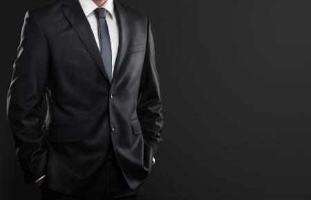 Primer plano de hombre de negocios en traje sobre fondo gris oscuro con copia espacio Foto de archivo