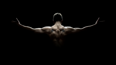 strong men: Rear view of healthy young man with his arms stretched out isolated on black background