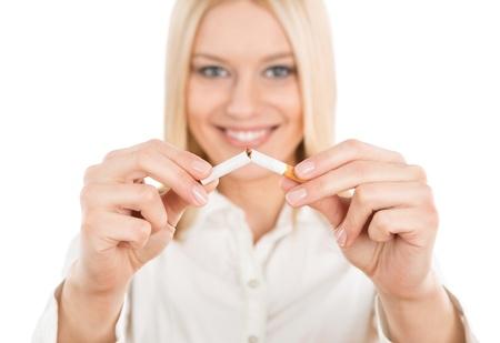 chica fumando: Deje de fumar, mujer rubia joven rompiendo un cigarrillo aislado sobre fondo blanco
