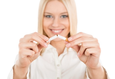 Quit smoking, young blonde woman breaking up a cigarette isolated on white background photo