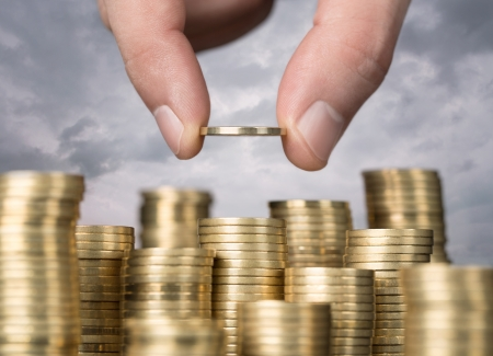 savings and loan crisis: Savings, close up of male hand stacking golden coins over sky background