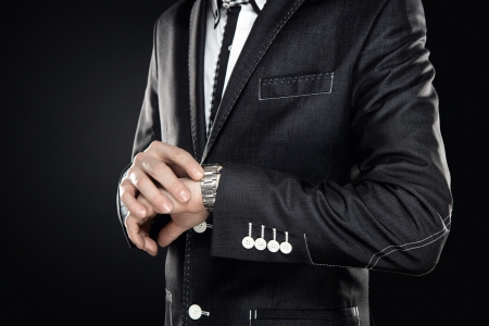 Close up of elegant man checking the time isolated on gray background with copy space