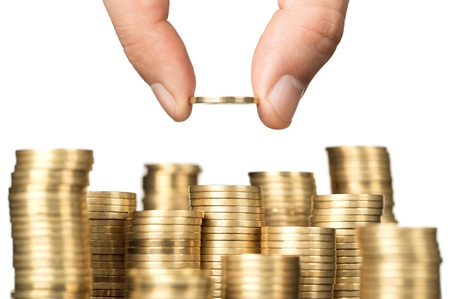 income: Savings, close up of male hand stacking gold coins isolated on white background