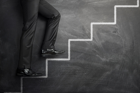 growth opportunity: Businessman climbing at the career stairs drawn on a black chalkboard with copy space